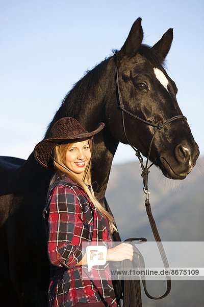 Young woman with a black Hanoverian horse  North Tyrol  Austria
