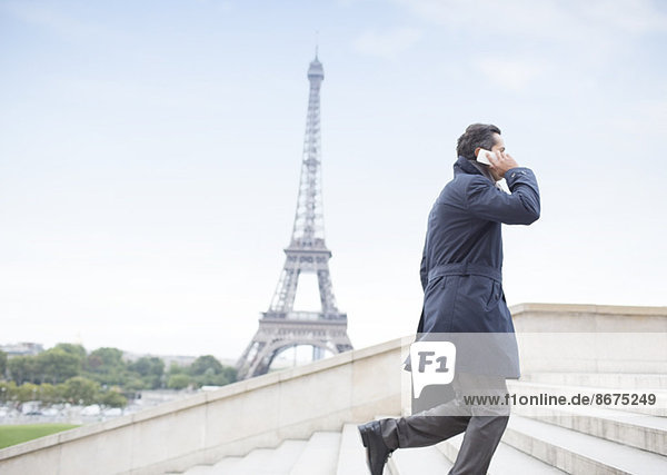Geschäftsmann im Gespräch am Handy und aufsteigende Stufen beim Eiffelturm,  Paris,  Frankreich
