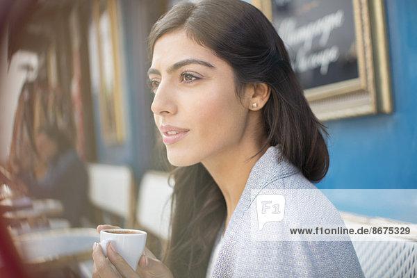 Woman drinking espresso at sidewalk cafe