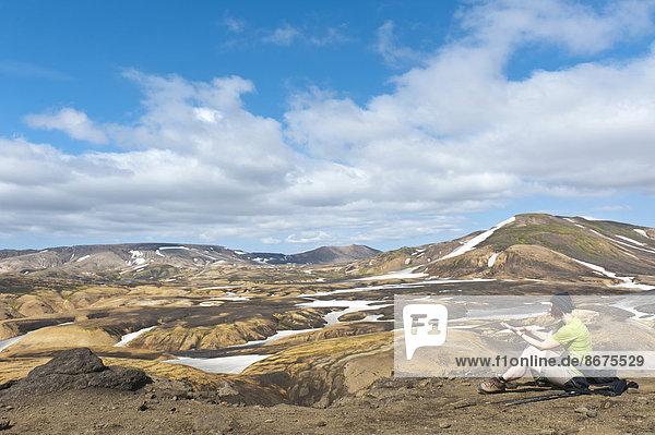 Trekking im Hochland  Frau rastet  weite Berglandschaft und Schneefelder  Trekkingweg Laugavegur  bei Hrafntinnusker  Rangárþing ytra  Suðurland  Island  Skandinavien