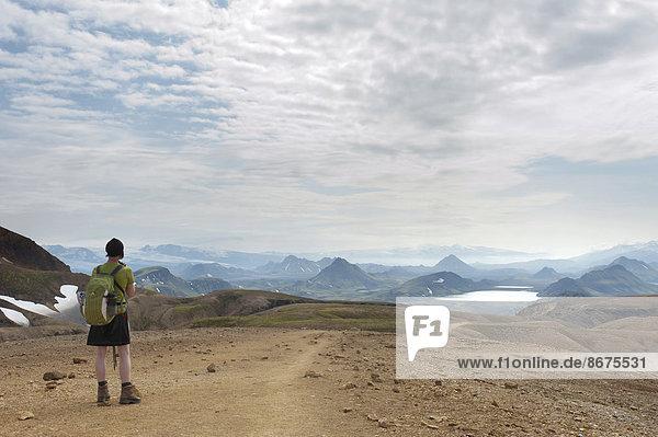 Trekking im Hochland  Frau mit weitem Ausblick in die Berglandschaft  Trekkingweg Laugavegur  bei See Álftavatn  Rangárþing ytra  Suðurland  Island  Skandinavien