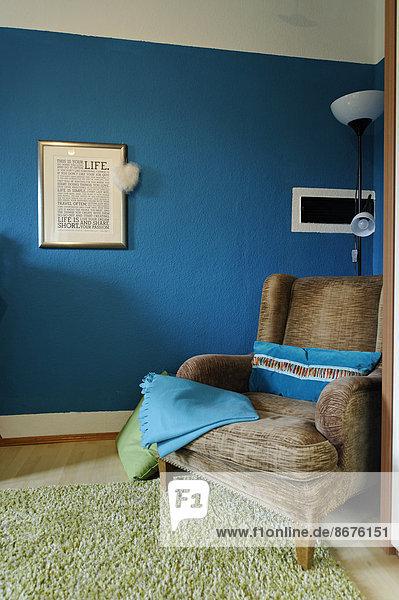 Flügelstuhl in einer Ecke eines Wohnzimmers vor einer blauen Wand stehend