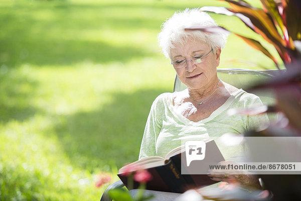 Außenaufnahme Senior Senioren Europäer Frau Buch Taschenbuch freie Natur vorlesen