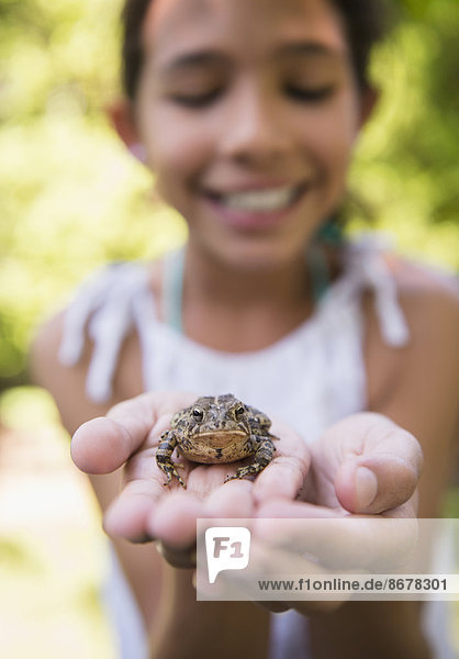 Mixed race girl holding frog outdoors