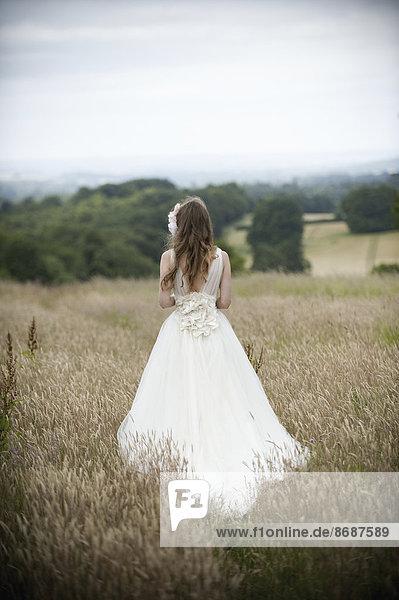 Eine Braut in ihrem Brautkleid  die auf einem Feld steht.