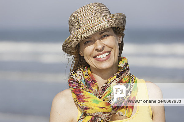 A woman in a sunhat and scarf on the beach on the New Jersey Shore  at Ocean City.