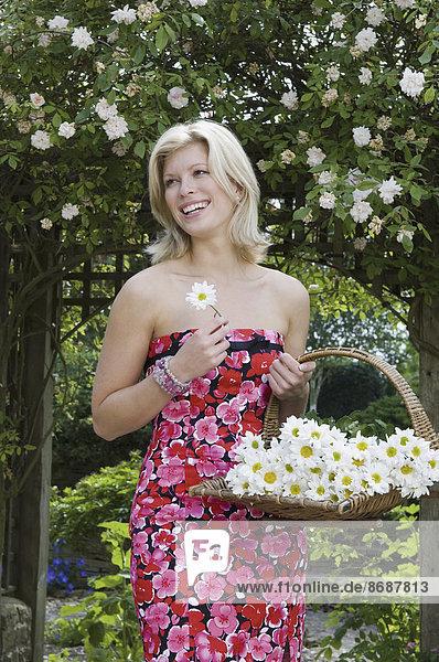 Eine junge Frau trägt einen Korb mit Schnittblumen.