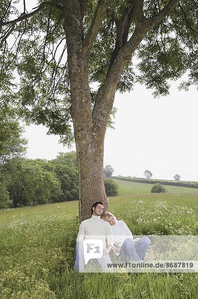 Ein Paar  das an einen Baum gelehnt auf einer Wiese sitzt.