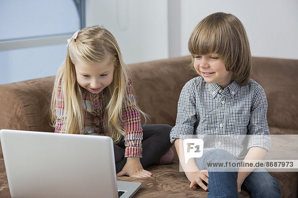 Happy boy with sister using laptop on sofa