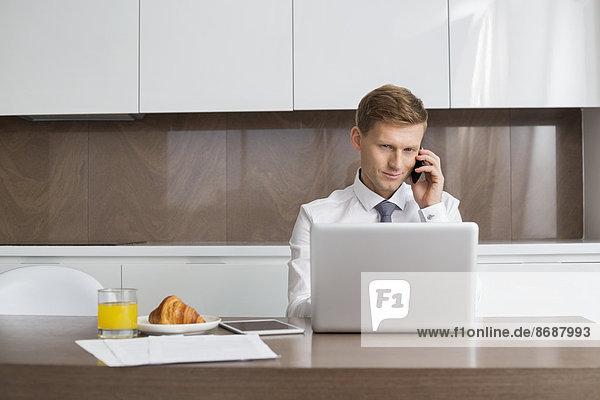 benutzen  Notebook  Geschäftsmann  Mittelpunkt  Gespräch  Gespräche  Unterhaltung  Unterhaltungen  Tisch  Erwachsener  Frühstück