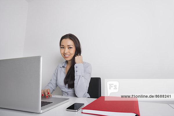 benutzen  Portrait  Geschäftsfrau  Schreibtisch  Fröhlichkeit  Notebook  Büro
