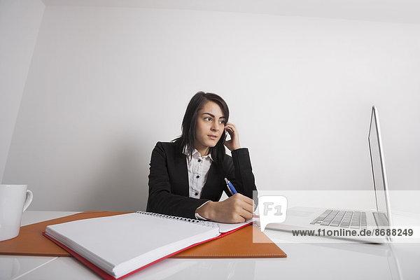 benutzen  Geschäftsfrau  Schreibtisch  Notebook  schreiben  Telefon  Büro  Handy