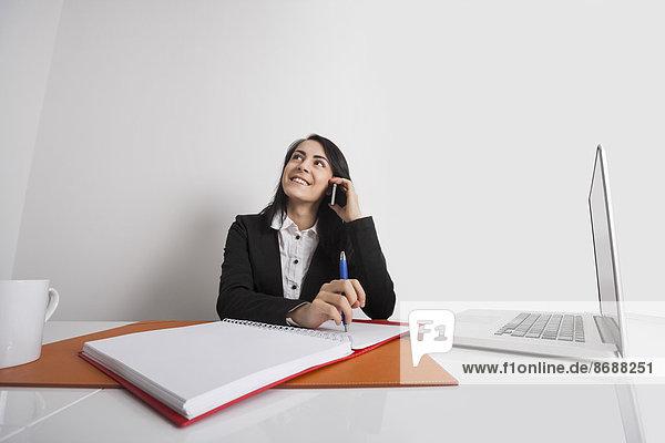 benutzen  Geschäftsfrau  Schreibtisch  Telefon  Büro  Handy