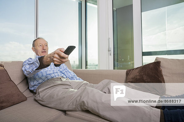 Senior man watching TV on sofa at home