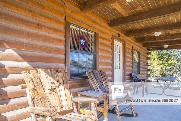 USA  Texas  Veranda eines Blockhauses mit Holzstühlen