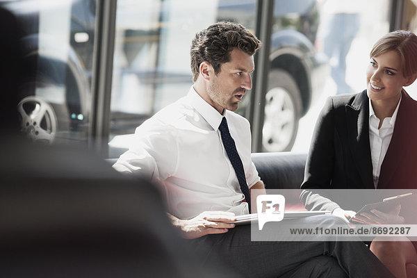Geschäftsmann und Geschäftsfrau im Gespräch in der Bürolobby