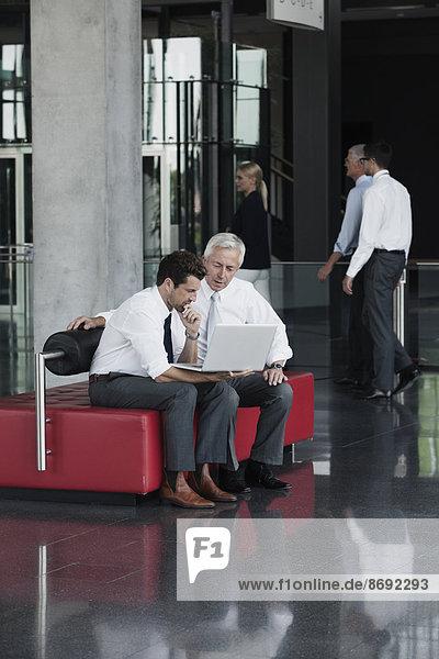 Zwei Geschäftsleute mit Laptop in der Büro-Lobby