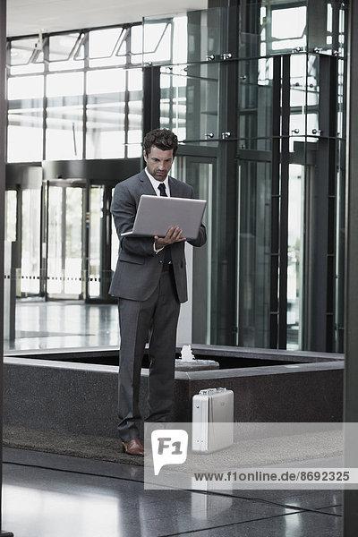 Geschäftsmann mit Laptop in der Büro-Lobby