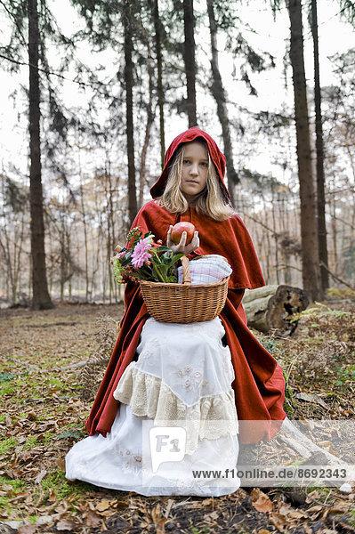 Mädchenmaskerade als Rotkäppchen auf einem Stamm im Wald sitzend