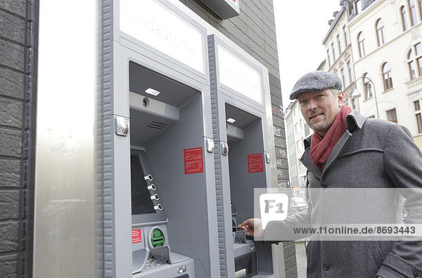 Man standing at cash dispenser