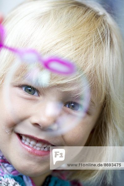 Portrait of smiling little girl with soap bubble