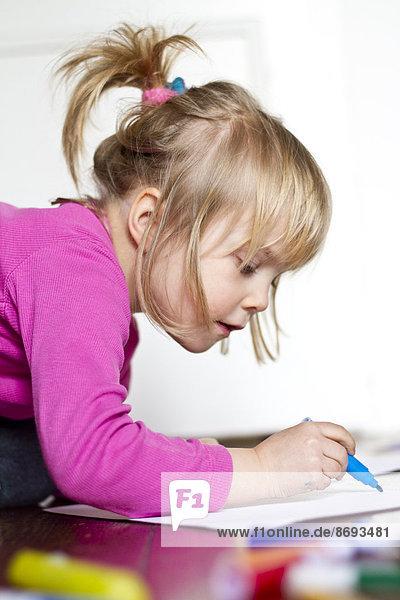 Little girl painting with blue felt tip pen