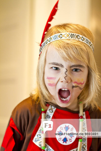 Portrait of crying little girl masquerade as Indian