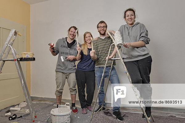 Group picture of four friends renovating apartment together