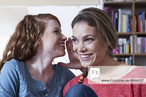 Zwei junge Freundinnen zu Hause  die sich vertraulich austauschen.