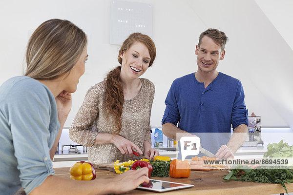 Drei Freunde beim Zubereiten des Essens und mit dem Tablet-Computer