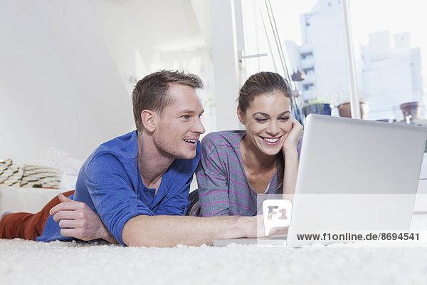 Paar zu Hause auf dem Teppich liegend mit Laptop