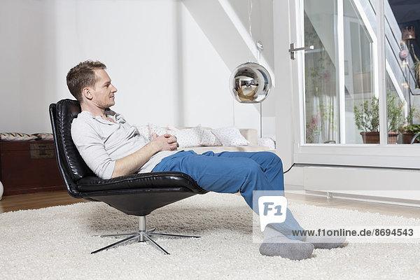 Mann zu Hause entspannt im Sessel