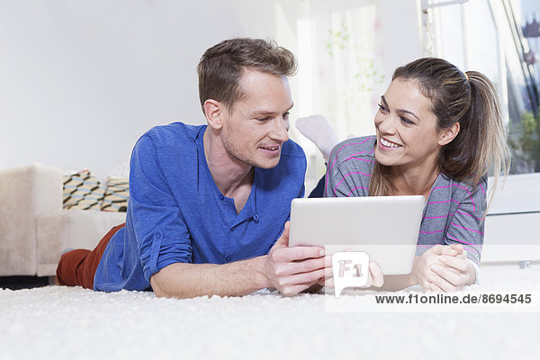 Couple at home lying on carpet and using tablet computer