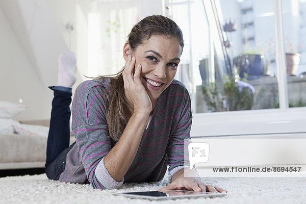 Frau zu Hause auf Teppich liegend und mit Tablet-Computer
