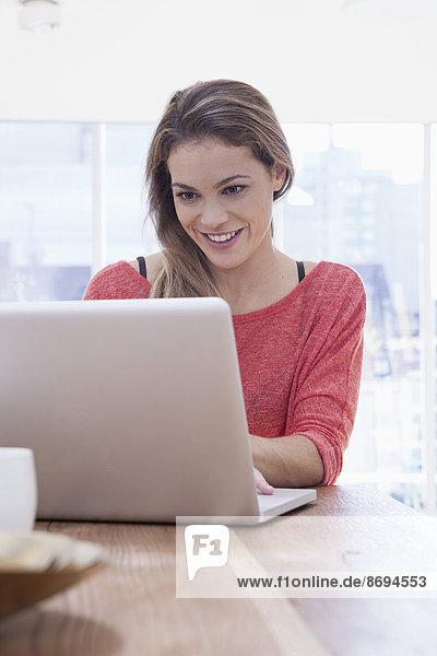 Frau mit Laptop zu Hause