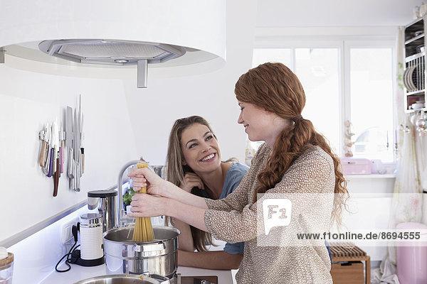Zwei junge Freundinnen beim gemeinsamen Kochen