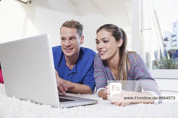 Paar zu Hause auf dem Teppich liegend und mit Laptop