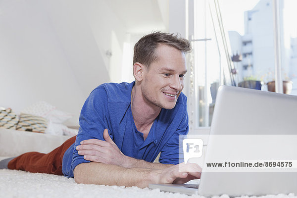 Mann zu Hause auf dem Teppich liegend und mit Laptop