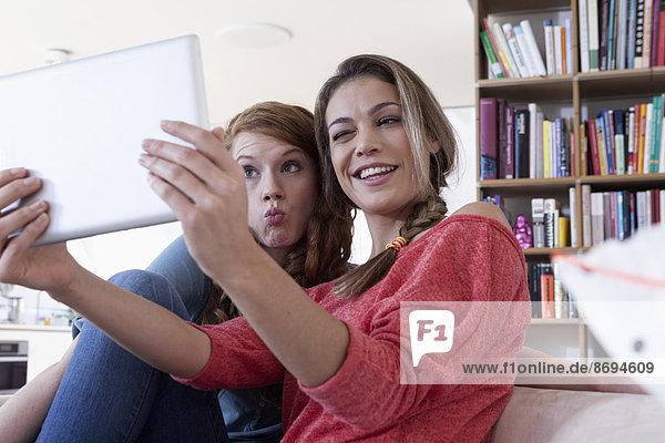 Zwei junge Freundinnen beim Fotografieren mit dem Tablet-Computer