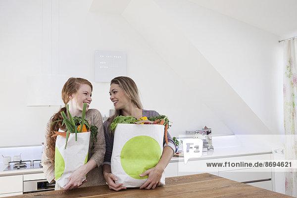Zwei Frauen halten Einkaufstaschen mit Einkäufen.