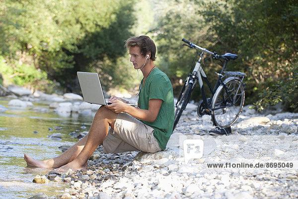 Österreich  Salzkammergut  Mondsee  junger Mann mit Laptop lernen am Bach