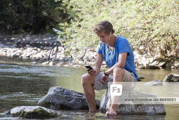 Österreich  Salzkammergut  Mondsee  junger Mann mit Handy zum Entspannen am Bach