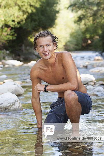 Austria  Salzkammergut  Mondsee  portrait of young man crouching in a brook