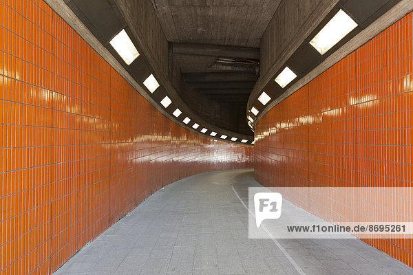 Eine hell beleuchtete orange Unterführung  Berlin  Deutschland