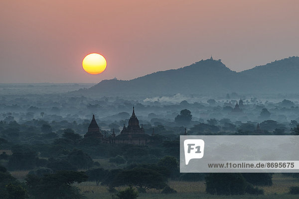 Sunrise  temples in the morning mist  stupas and pagodas in the temple complex of the Plateau of Bagan  Mandalay Division  Myanmar or Burma
