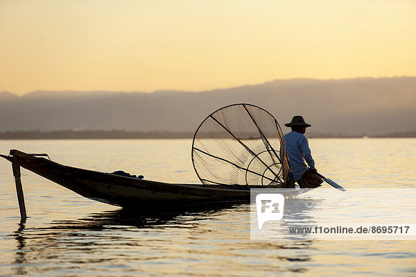 Fisherman in the evening light  with a traditional basket  sitting on a canoe  sunset at Inle Lake  Shan State  Myanmar