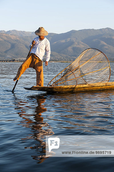 Fisherman  leg rower with a traditional basket on the canoe  Inle Lake  Shan State  Myanmar