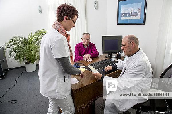 Arztpraxis  älterer Patient im Gespräch mit seinem Hausarzt  Sprechstundenhilfe  Deutschland