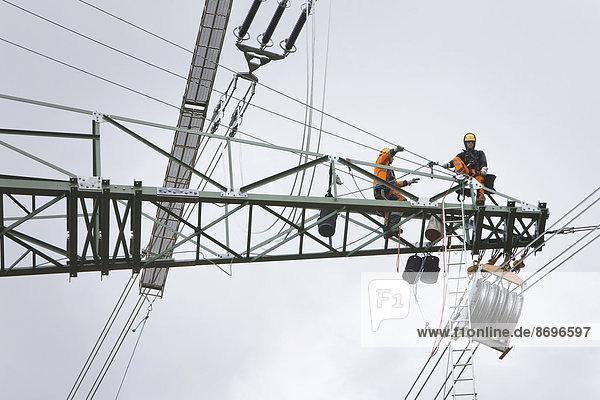 Freileitungsmonteure bei Leiterseilzugarbeiten auf der Traverse eines neu errichteten Höchstspannungsmastes  Mönchenholzhausen  Thüringen  Deutschland