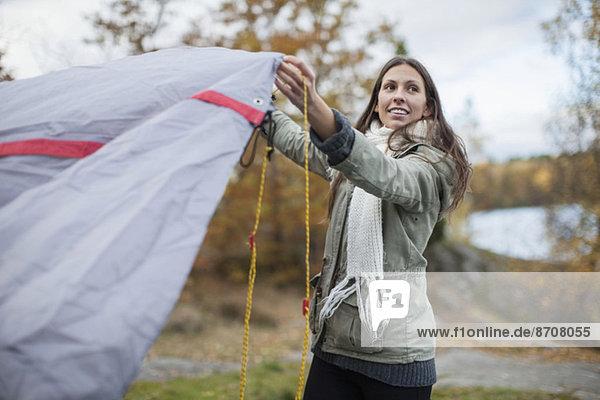 Junge Frau beim Aufstellen des Zeltes im Wald